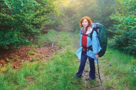 Red hired caucasian girl hiking in the forest with her backpack on Stock Photo - 16272993