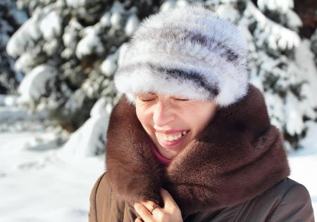 screwing: Girl screwing up her eyes on bright dazzling sun in winter Stock Photo