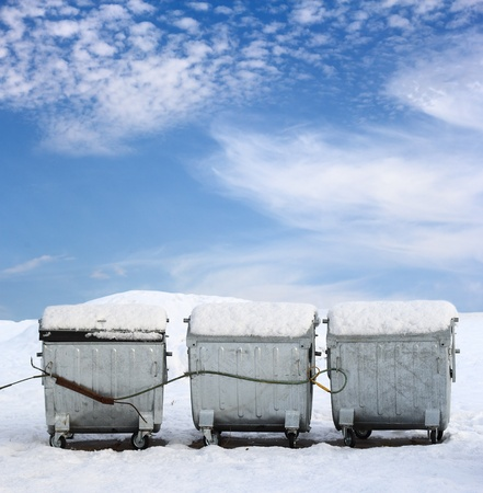 Three old metal garbage containers over blue cloudy sky photo