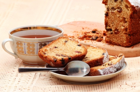 Sliced cake with raisins on a the plate with a cup of tea Stock Photo