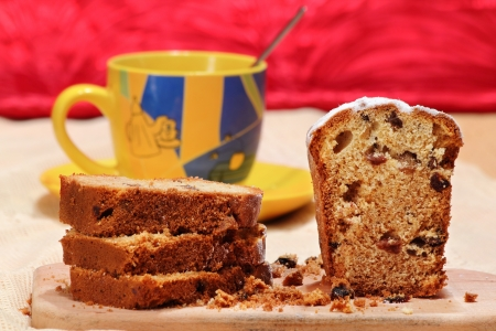 Cut cake with raisins on a breadboard over a cup of tea on the background