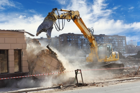 construct site: Bulldozer crushing the building at construction site