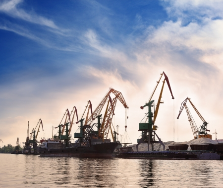 Cargo cranes in the dock by the water over blue sky Stock Photo