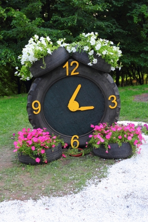 Rubber tyres with petunia flowers on them forming a clock Stock Photo