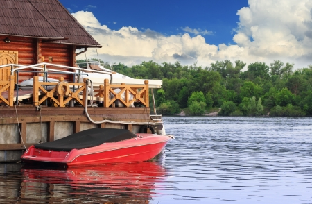 river scape: Docked red boat over picturesque cloudy river scape