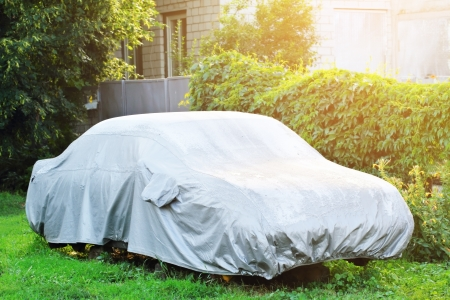 Een geparkeerde auto met beschermkap bij nat weer