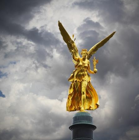 嵐の曇り空でミュンヘンで平和の黄金の天使 写真素材