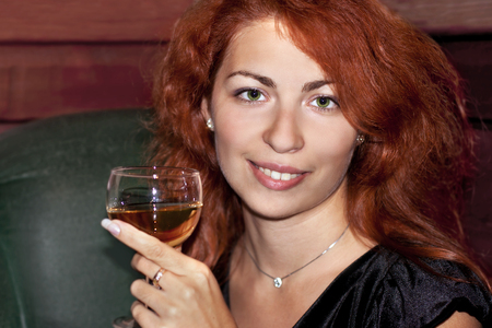 red haired woman: A young red haired woman having a glass of wine in the restaurant