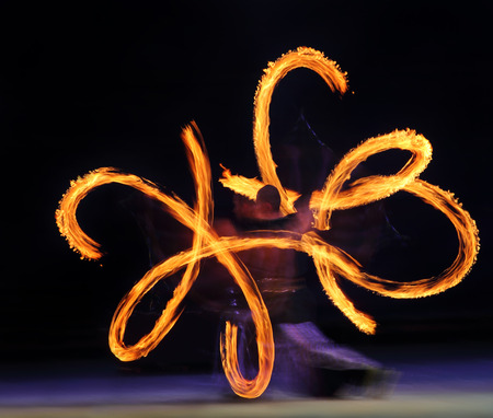 Artist juggling with two burning pois at fire performance. Long exposure causing painting with light