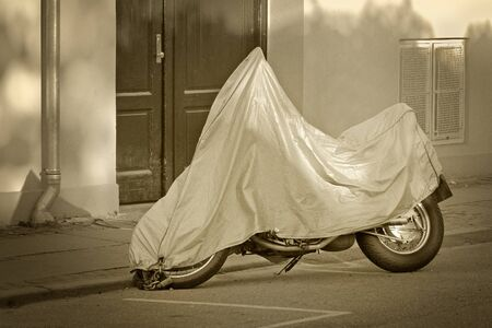 A parked scooter with protective cover at the street
