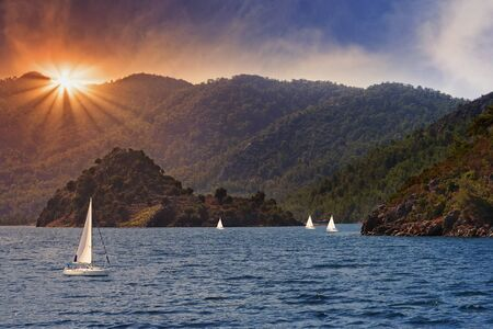 woody bay: Evening view on the island in Eagean sea full of yachts, Turkey Stock Photo