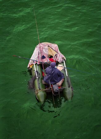 inflatable boat: The fisherman in the inflatable boat enjoys fishing Stock Photo