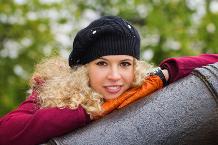 brown  eyed: Gently looking blond curly girl leaning on the cannon in the park