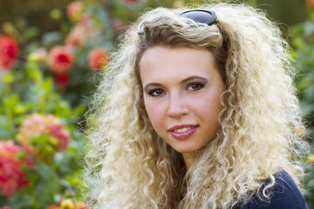 brown  eyed: Beautiful blond curly girl enjoying flower garden