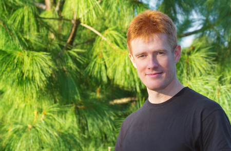 Young red haired guy engoing the walk through the pinery
