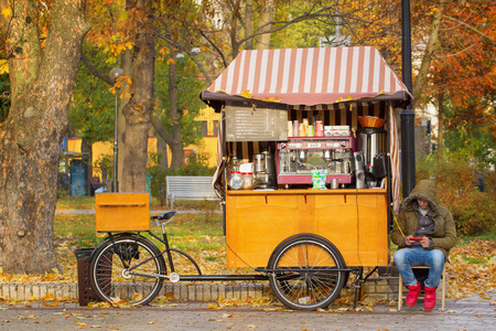 selling points: UKRAINE, KIEV - NOVEMBER 4, 2015: A man selling coffee drinks by his bike shop in autumnal park, Kiev, Ukraine