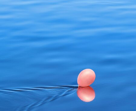 easing: A pink balloon floating on the water under the wind blast Stock Photo