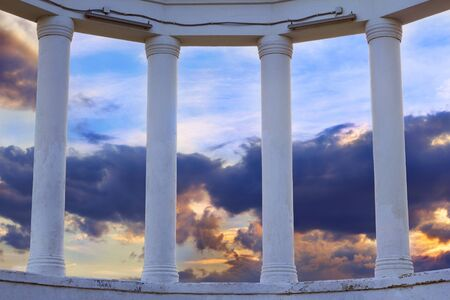 greek columns: View on dramatic cloudy sunset sky through the greek columns