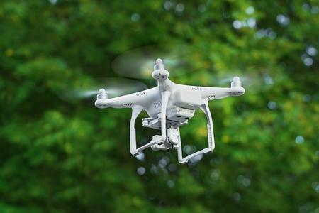 KIEV, Ucrania - 14 de julio, 2016: Primer plano de un avión no tripulado blanco quadrocopter volando sobre los árboles en el parque. Editorial