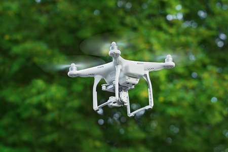 KIEV, UKRAINE - JULY 14, 2016: Closeup of a white drone quadrocopter flying over the trees in the park. Editorial