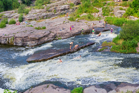 personas banandose: BUKY, CHERKASY REGION, UKRAINE - JULY 2, 2016: People bathing in the river of Buky canyon in Cherkasy region, Ukraine Editorial