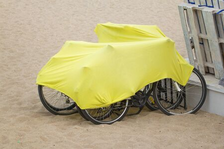 to conceal: Bicycles on the beach covered with protective mantle