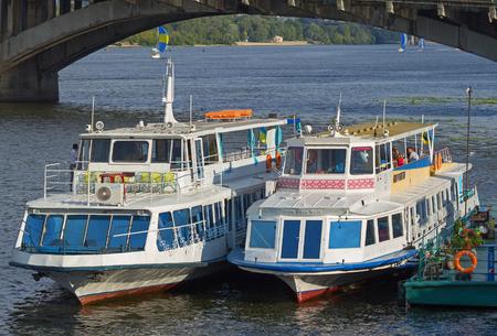 motorizado: Kiev, Ukraine - August 24, 2016: Closeup of pleasure boats docked near the bridge in Dnieper river, Kiev, Ukraine