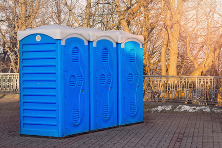 A row of bio toilets in public place hit by the sun Stock Photo