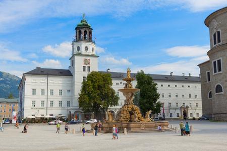 Salzburg, Austria - 3 September, 2016: Tourists walking at Residenzplatz in Salzburg. View on baroque fountain and Salzburg museum (Salzburger Glockenspiel), Austria, Europe Editorial