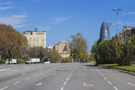 Barcelona, Spain - 26 March, 2017: View on the typical street of Barcelona and Torre Agbar busines center.
