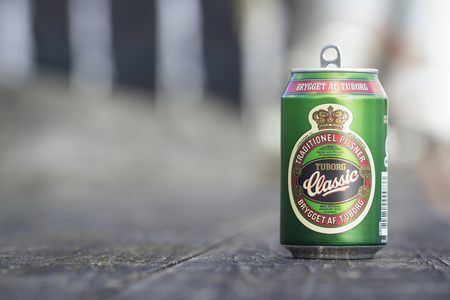 tin: Copenhagen, Denmark - 16 September, 2017: Drinking Tuborg classic from the tin can at sunny weather in Copenhagen at the river bank. Editorial