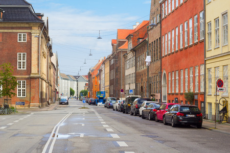 Copenhagen, Denmark - 17 September, 2017: Typical street in Copenhagen with colorful buildings and cars parked on it.