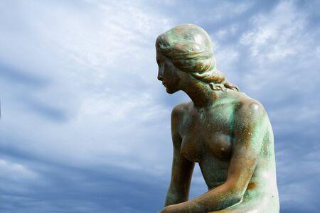 Copenhagen, Denmark - 17 September, 2017:  Little Mermaid statue sitting on a rock on the harborfront in the northern Kastellet area.