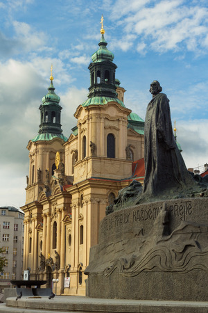 The Jan Hus monument at the old town square and St. Nicholas church in Prague, Czech Republic during day Stock Photo