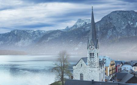 View on the foggy Halstatt and Protestant parish church, Austria Stock Photo