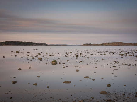 Hundreds of small rocks lying on the sea bed is exposed because of the low tide. It is a quiet early spring morning. The water is still like a mirror with diffuse clouds reflecting in this seascape.