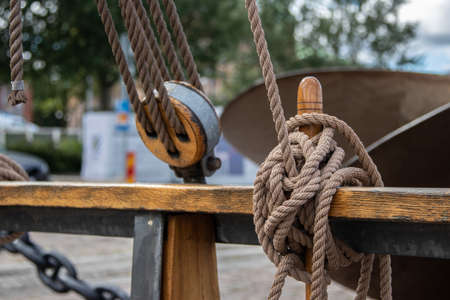A wooden block with ropes tied to the railing on an old sailing ship