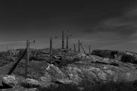 Electric fence in a rocky landscape in perspective and monochrome