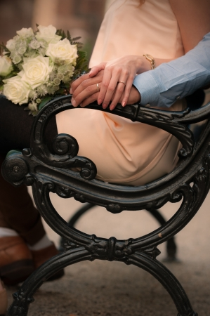 chear: Man and woman sitting on a romantic chear, wedding rings seen