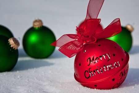Merry Christmas Jingle Bell with Green Ornaments in the Snow photo