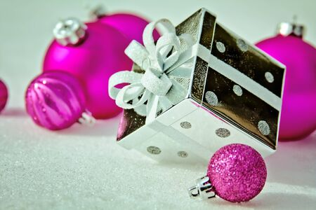 Silver Present and Pink Ornaments in the Snow Stock Photo