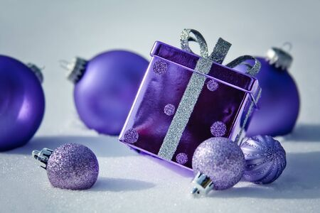 Purple Present and Purple Ornaments in the Snow Stock Photo