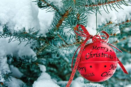 Red Merry Christmas Ornament Hanging on a Snowy Pine Tree photo