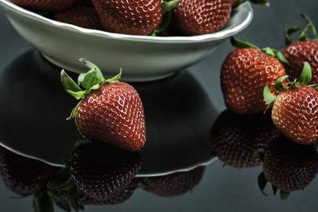 Fresh Strawberries in White Bowl on Black Plexiglass Reklamní fotografie