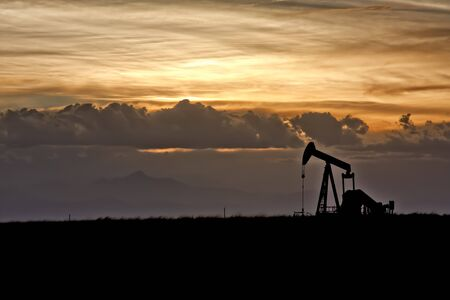 Dramatic Sunset Skies Over Oil Field and Oil Well photo
