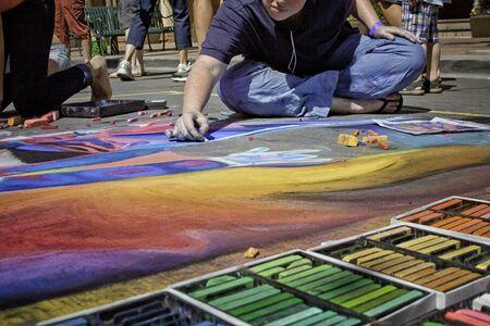Sidewalk Chalk Artist Drawing with Rainbow of Chalk