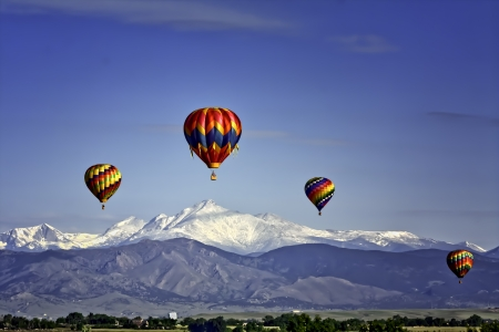 Multi-Colored Hot Air Balloons Over Snowy Peaks
