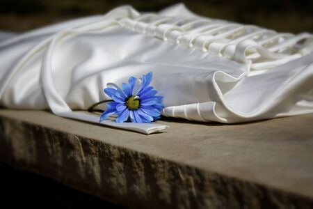 alter: Wedding dress laying on alter with blue flower, close up