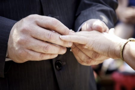 Groom putting wedding ring on bride s finger photo