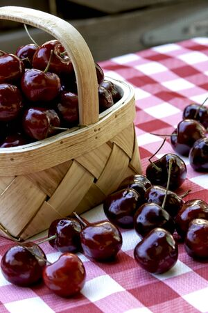 Black Cherries in Wicker Basket on Checkered Tablecloth, with Heart Cherry in Front
